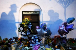 Bystanders and mourners cast shadows on the walls and the makeshift memorial at the Emanuel African Methodist Episcopal Church in Charleston